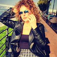 La Force zadovoljna mušterija nosi crnu kožnu jaknu, dok sedi i uživa u jesenjem suncu