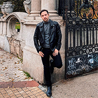 Zadovoljni kupac nosi rokersku crnu kožnu jaknu La Force, dok stoji naslonjen na zid